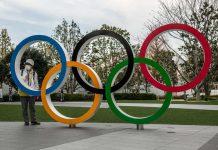 Japonka stojaca pri olympíjskych kruhoch v rúške