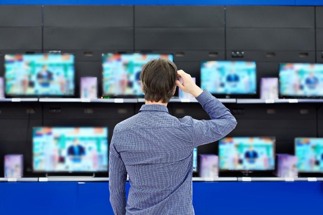 Muž vyberajúci vhodný televízor